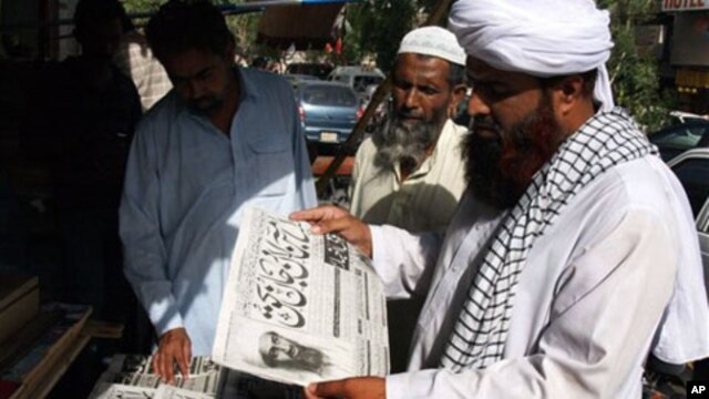 "People read newspapers at a news stand carry headlines ""Osama bin Laden killed."" in Hyderabad, Pakistan on Monday, May 2, 2011."