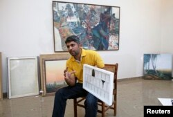 Imran Mudassar, 31, a fine art teacher, shows his latest piece Government College University in Lahore, March 22, 2013.