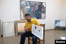 Imran Mudassar, 31, a fine art teacher, shows his latest piece Government College University in Lahore, March 22, 2013.