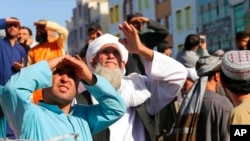 Ljudi gledaju u tela ubijenih koje su talibani obesili o kran na glavnom trgu u gradu Heratu, u zapadnom Avganistanu, 25. septembra 2021.