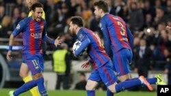 Lionel Messi de Barcelone, au centre, court, balle en main, en compagnie de ses co-équipiers Neymar, à gauche, et Gerard Piqué, après son but sur penalty lors d'un match de la Ligue des champions entre le FC Barcelone et Paris Saint Germain au stade Camp