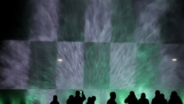 People are silhouetted as they watch a night fountain show with color lights near the Centennial  Hall in Wroclaw, Poland, Thursday, Oct. 7, 2010.(AP Photo/Alik Keplicz)