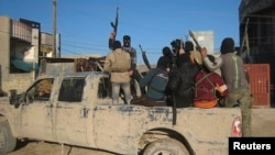 FILE - Masked Sunni gunmen, likely belonging to the group Islamic State of Iraq and the Levant (ISIL), are seen in the city of Falluja Feb. 8, 2014.