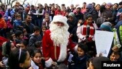 """Enfants migrants reassembles autour d'un volontaire habille en peer Noel, rencontre facilitee par une organization humanitaire locale """"Die Johanniter"""" au camp des refugies a Hanau, Germany, Dec. 24, 2015.REUTERS/Kai Pfaffenbach -"""