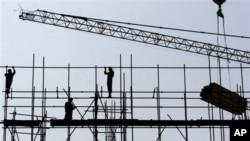 FILE - Chinese construction workers labor at a highrise building under construction in Beijing.