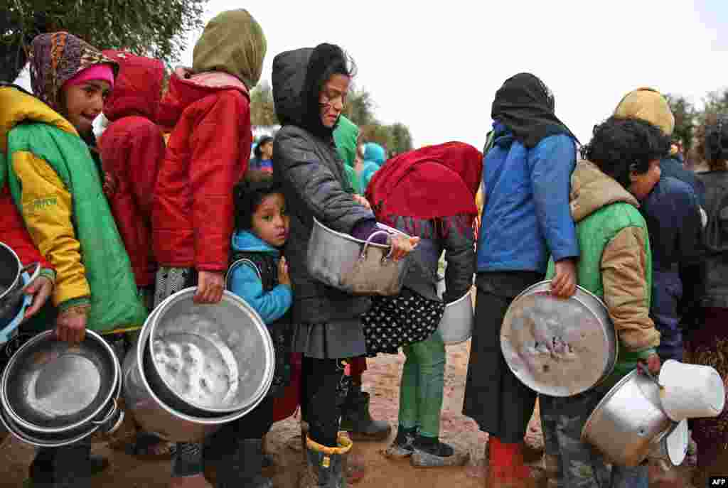 Syrian children queue to receive food distributed by humanitarian aid workers at a makeshift camp for displaced people, near the village of Yazi Bagh, about six kilometers from the Bab al-Salamah border crossing between Syria and Turkey in the north of Aleppo province.