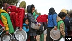 Syrian children queue to receive food distributed by humanitarian aid workers at a makeshift camp for displaced people, near the village of Yazi Bagh. (File)