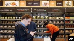FILE - Shoppers roam through an Amazon Go store, currently open only to Amazon employees, in Seattle, Washington, April 27, 2017.