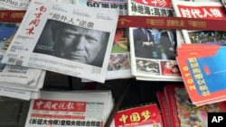 "FILE - front page of a Chinese newspaper with a photo of U.S. President-elect Donald Trump and the headline ""Outsider counter attack"" is displayed at a newsstand in Beijing, China."