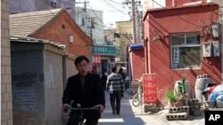 Man rides through the heart of Caochangdi Village