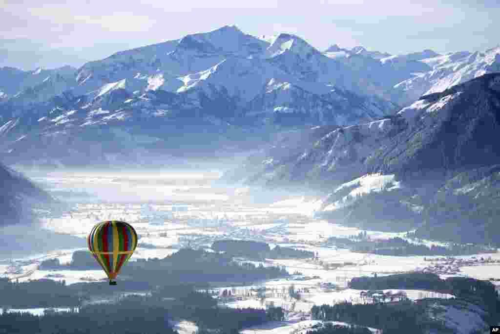 A hot air balloon floats above Zell am See, Austria.