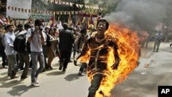 A Tibetan man screams as he runs engulfed in flames after self-immolating at a protest in New Delhi, India, ahead of Chinese President Hu Jintao's visit to the country Monday, March 26, 2012. The Tibetan activist lit himself on fire at the gathering and w