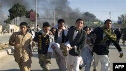 Avganistanci nose čoveka povredjenog u napadu na kancelariju UN za vreme demonstracija zbog spaljivanja Kurana koje je počinio pastor sa Floride.