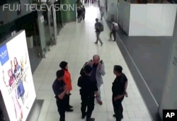 FILE - Kim Jong Nam gestures toward his face while talking to airport security and officials at Kuala Lumpur International Airport.