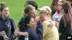 Para siswa saling berpelukan sementara dipertemukan dengan para orang tua mereka pasca penembakan di SMA Saugus di Santa Clarita, California (14/11).