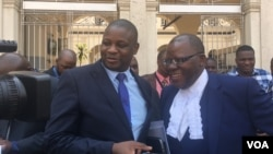 Tendai Biti, (R), opposition leader and member of Zimbabwe Lawyers for Human Rights, and Dzimbabwe Chibga from the rights group talk to reporters outside the High Court in Harare, Zimbabwe, September 2016. The two represented Zimbabwean opposition parties in court. (S. Mhofu/VOA)