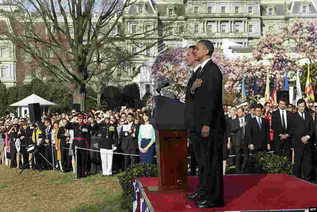 Mr. Obama and Mr. Cameron stand at attention during the playing of the national anthems during an arrival ceremony on the South Lawn of the White House. (AP)