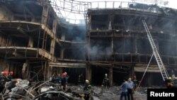 3일 바그다드 카라다 상업지구의 폭탄 테러 현장에 사람들이 모여 있다.