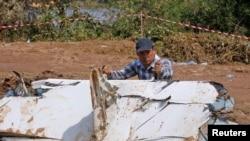 调查人员在失事的老挝飞机残骸碎片边工作。