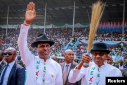 Nigeria's President Muhammadu Buhari, at right, greets supporters during a campaign rally in Rivers State on Feb. 12, 2019. He seeks a second term in the election Saturday.