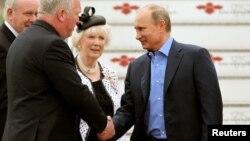 El presidente ruso Vladimir Putin (derecha) es recibido a su llegada al aeropuerto internacional de Belfast.
