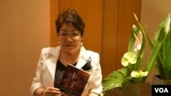 远藤誉接受美国之音采访时,展示早已被译成中文的《卡子》(美国之音歌篮拍摄)