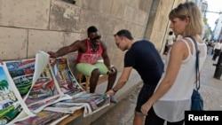 A man shows tourists prints for sale in Old Havana, Cuba, Dec.18, 2014.