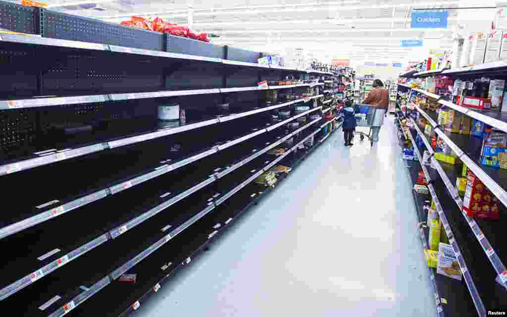 A woman and child walk through an aisle emptied in preparation for Hurricane Sandy, in a Wal-Mart store in Riverhead, New York, October 28, 2012.