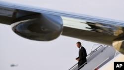 باراک اوباما در حال پایین آمدن از پله های هواپیما در پایگاه هوایی سنت اندروز در مریلند پس از سفر عربستان، بریتانیا و آلمان