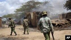 Polisi Kenya melakukan patroli melewati rumah-rumah yang hangus terbakar di desa Nduru, pasca terjadinya bentrokan antara para petani dan penggembala ternak di Sungai Tana, Kenya bagian tenggara, September lalu (Foto: dok). Sedikitnya 28 orang tewas dalam bentrokan etnis yang kembali terjadi di wilayah ini, Jum'at (21/12).