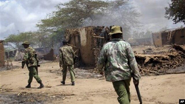 Polícias quenianos patrulham por entre os escombros das casas de aldeões destruídas pela violência inter-étnica desta Sexta-feira no Delta do Tana, situado no sudeste do país