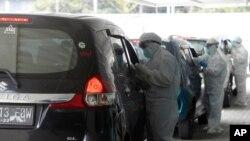 Petugas mengenakan APD, saat melakukan tes swab Covid-19 di Jakarta, Senin, 12 Oktober 2020. (AP Photo / Achmad Ibrahim)