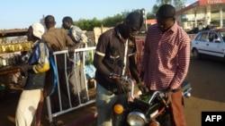 Un homme achète de l'essence au marché noir pour sa moto dans le quartier Lazaret de Niamey, le 5 janvier 2012.