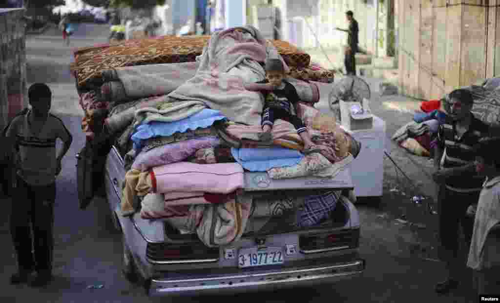 A Palestinian boy sits atop a car loaded with his family's belongings near their house, which was hit by an air strike, in Rafah in the southern Gaza Strip, Aug. 26, 2014.