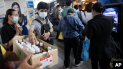 Commuters wearing face masks to protect themselves from new virus take clean gel for hands during a campaign for washing hands at the skytrain station in Bangkok, Thailand, Friday, Feb. 7, 2020. (AP Photo/Sakchai Lalit)