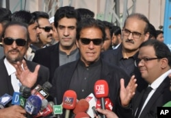 In this Tuesday, Jan. 2, 2018, photo, Pakistan's opposition leader Imran Khan, center, speaks to the media in Islamabad, Pakistan.