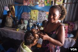Mary Sanyu, a hairdresser, poses for a photograph in her salon at Konyo Konyo market in Juba, South Sudan on April 15, 2016. (VOA/J. Patinkin)