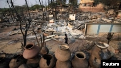 A man walks past homes burned down during the riot in Meikhtila, March 23, 2013.