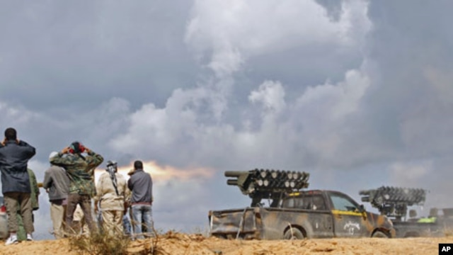 National Transitional Council fighters fire a rocket during clashes with pro-Gadhafi forces at the frontline in Sirte, Libya, October 11, 2011.