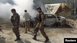 Lực lượng an ninh Afghanistanđi ngang một chiếc xe đang bốc cháy sau khi một nhóm phiến quân xông vào một khu nhà do cơ quan tình báo của Afghanistan sử dụng ở Kabul, ngày 7 tháng 7, 2015.