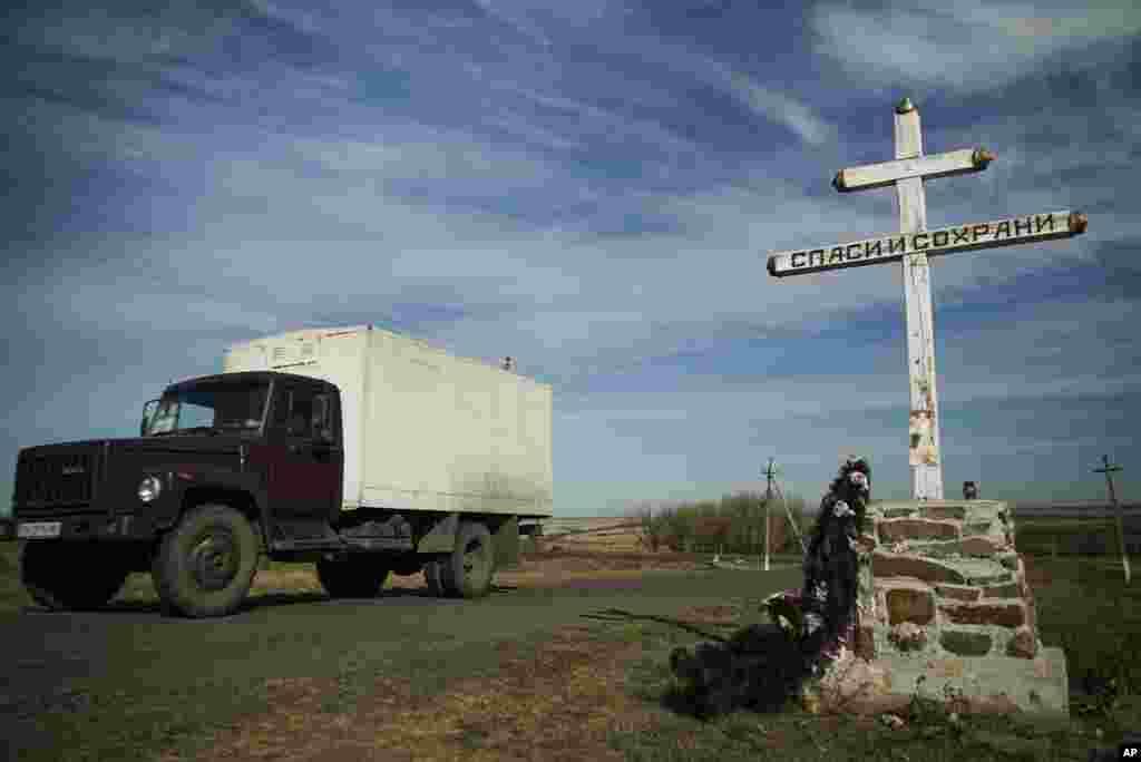 Sebuah truk melewati salib Ortodoks dengan papan bertuliskan Menyelamatkan dan Menjaga, di tempat memorial untuk para korban jatuhnya pesawat Malaysian Airlines bernomor penerbangan MH17, dekat desa Hrabove, Ukraina timur (13/10). (AP/Mstyslav Chernov)
