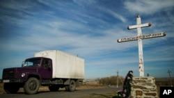 """Sebuah truk melalui tanda salib Ortodoks bertuliskan """"Selamatkan dan Jagakan"""" di area peringatan jatuhnya pesawat MH17 di Ukraina."""