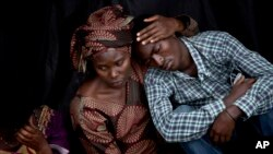 Bizimana Emmanuel, who was born two years before the genocide, is consoled by an unidentified woman while attending a ceremony to mark the tragedy's 20th anniversary, Kigali, April 7, 2014.