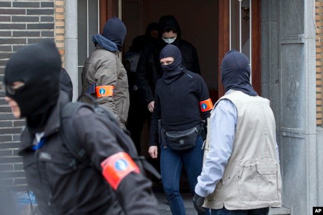 Belgian police leave after an investigating in a house in the Anderlecht neighborhood of Brussels, Belgium, March 23, 2016, one day after Tuesday's deadly suicide attacks on the Brussels airport and its subway system.