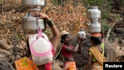 FILE - A woman helps another in carrying metal pitchers filled with water from a well outside Denganmal village, Maharashtra, India, April 20, 2015.
