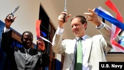 FILE - U.S. Ambassador to Tanzania, Mark Green, right, cuts a ribbon during a dedication ceremony at Jitegemee Secondary School in Dar es Salam, Tanzania, Dec. 18, 2008.