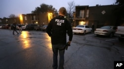 FILE - U.S. Immigration and Customs Enforcement agents enter an apartment complex looking for a specific undocumented immigrant convicted of a felony during an early morning operation in Dallas, March 6, 2015.