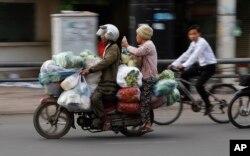 지난 16일 캄보디아 프놈펜에서 오토바이 택시 운전수가 손님과 짐을 오토바이에 태우고 이동하고 있다.