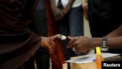 Seorang petugas tengah memeriksa sidik jari salah seorang pemilih di Daura, barat laut Nigeria, 28 Maret 2015 (REUTERS/Akintunde Akinleye)