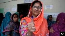 Seorang pemilih perempuan memperlihatkan jempolnya yang bertanda tinta setelah memberikan suaranya dalam pemilihan umum di Lahore, Pakistan (11/5). (APK.M. Chaudary)